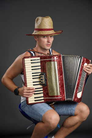 Portrait of a man in straw hat playing on accordion