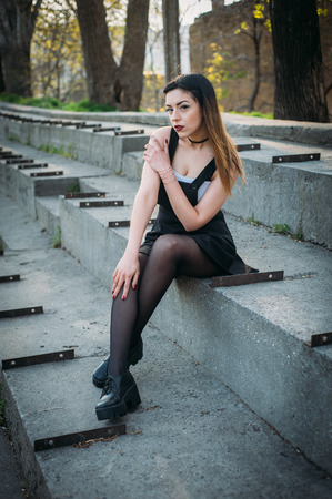 elegant staircase: Fashion pretty woman model wearing a balck sarafan. Sitting on the stairs of abandoned stadium