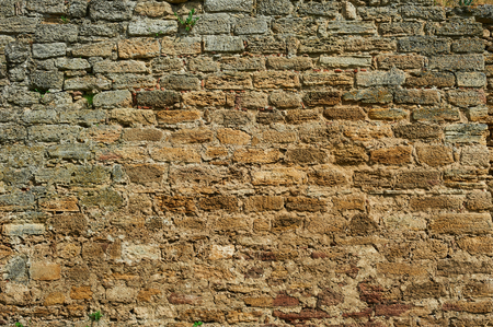 Ancient stone wall. Yellow grunge texture of old brick. Stock Photo