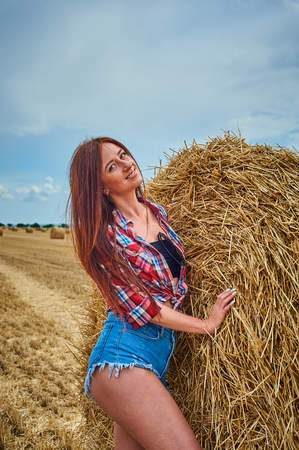 Portrait of young redhead woman in jeans shorts. Cowgirl and haystack against blue sky with clouds. Summer field with hay.