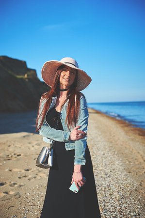 Redhead girl wearing black dress and jeans jacket. Straw hat. Holding smartphone. Woman standing on sand. Retro toned image. Stock Photo