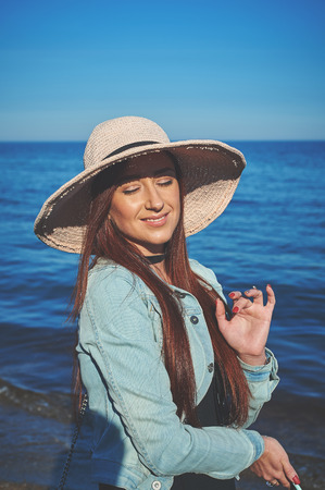 Redhead girl wearing black dress and jeans jacket. Straw hat. Woman standing on sand. Retro toned image.