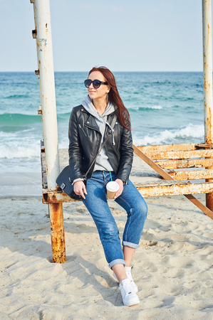 Beautiful young redhead woman in black leather jacket sitting on the old abandoned lifeguard tower at the beach near the ocean. Spring/fall season concept. Stock Photo