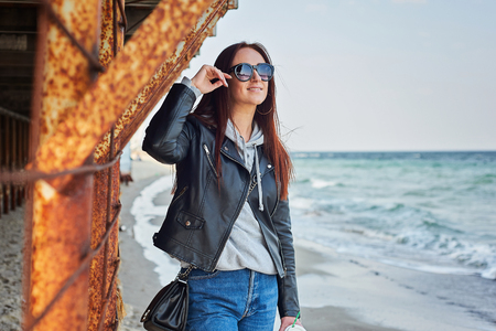 Beautiful young redhead woman in black leather jacket staying at the beach near the ocean. Spring/fall season concept. Old abandoned construction