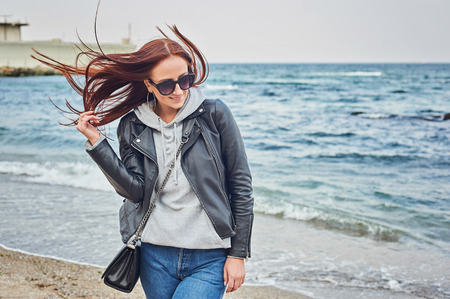 Beautiful young redhead woman in black leather jacket staying at the beach near the ocean. Spring/fall season concept. Stock Photo