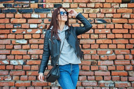 Beautiful young redhead woman in black leather jacket posing near the old grunge brick wall. Spring/fall season concept. Stock Photo