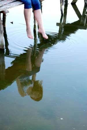 女の子座る水反射と小さな橋の上