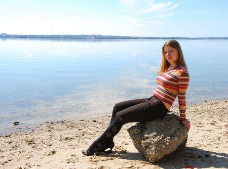 川岸に石の上に座っている女の子