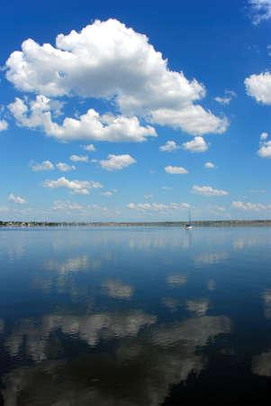 穏やかな水で曇った青空の反射