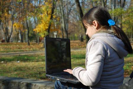 秋の公園でラップトップを持つ少女 写真素材