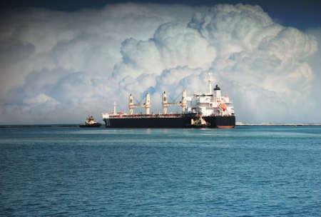 タグボートは、海に大きな船をプッシュします。 写真素材