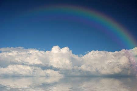 青い空に虹と白いふわふわの雲 写真素材