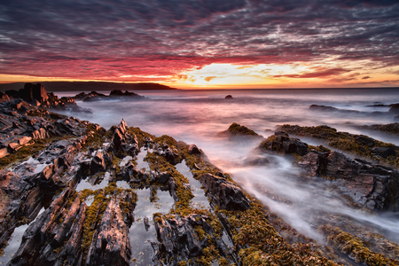 crimson colour: Sea sunset.The coast of the Barents sea. Stock Photo