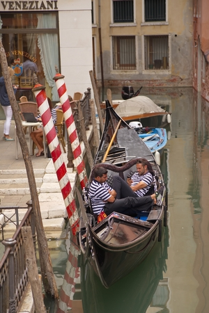 gondoliers: VENICE, ITALY - September 7, 2014: Gondoliers sitting in their gondola and awaiting tourists on September 7, 2014 in Venice, Italy. Editorial