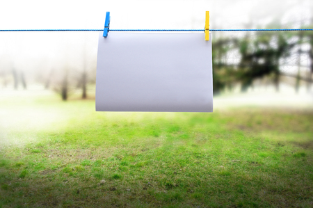 A sheet of paper on a rope with clothespins on a blurred background 写真素材