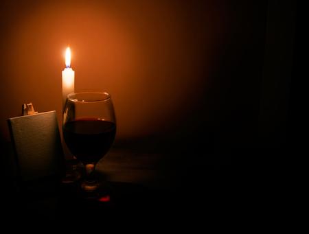 Stilleven van een kaars een glas wijn en een ezel