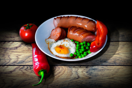 Vintage breakfast on wooden table of fried peas and peas sausages pepper and tomato 写真素材