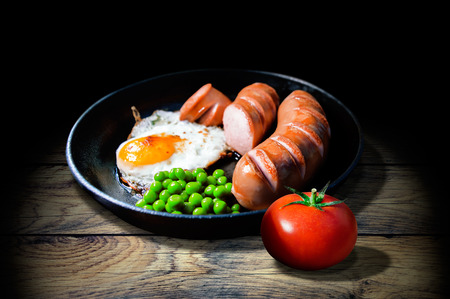 Breakfast of fried eggs, sausages, peas and tomato on a wooden old table 写真素材