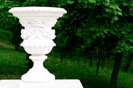 Antique decorative vase on the background of the city park