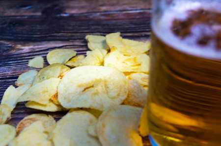 Chips and a glass of fresh beer closeup on a wooden table