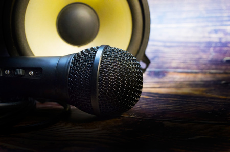Closeup with microphone and speaker on vintage wooden table. Reklamní fotografie