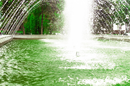 City fountain spraying water early summer in the park