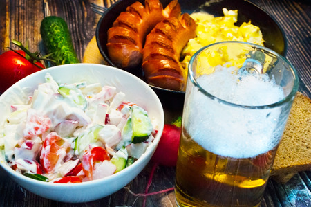 Glass of beer, salad and wieners with eggs on the background of vegetables