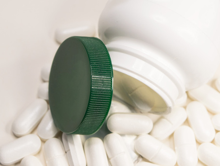 Closeup jar and white pills scattered on white background