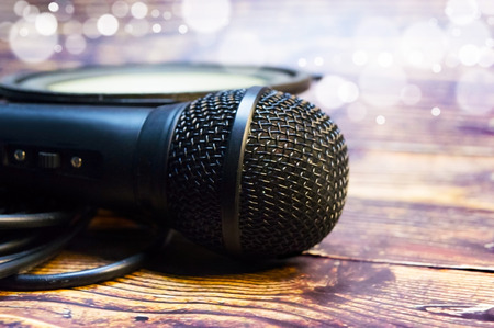 Microphone and speaker on the background of blurry particles and wooden table