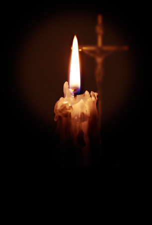 A burning candle in the foreground and a cross with a crucifix in the background.