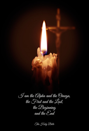 A candle and a cross and a quote from the Bible on a dark background. Imagens