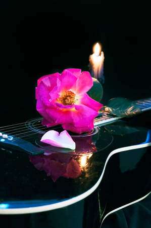 Beautiful musical composition guitar rose and candle.