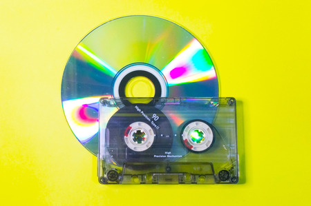 Compact disc and audio cassette on a yellow background.