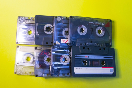 Audio cassettes are lined up on a yellow background.
