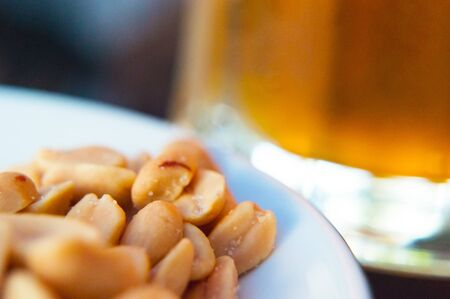 Cold frothy beer and salted nuts close up Imagens