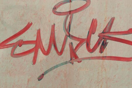 Background of a wall with graffiti painted in red font close-up Imagens