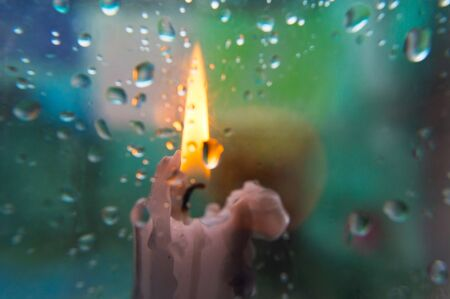 Raindrops on glass and blurred background with a candle in the front