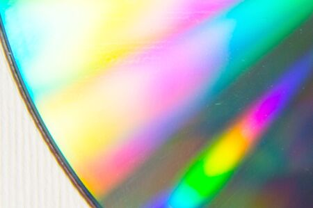 In the foreground a compact disc with an ultraviolet color palette in the background