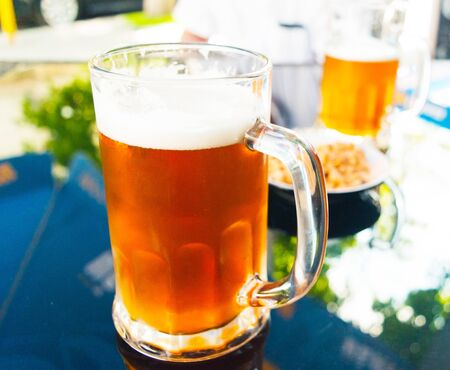 A glass of fresh light and cold beer on a blurred background