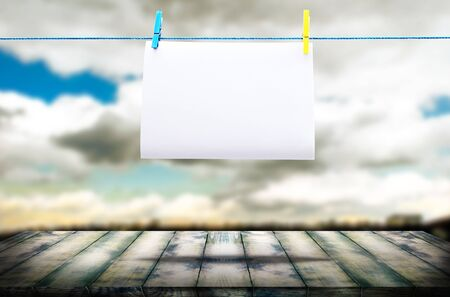 Wooden board in perspective, against the background of a blurred sky and a blank sheet of paper on a rope. The template can be used to display your products and advertisements.