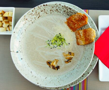 A plate of Creamy Mexican soup with bread crumbs and mushrooms.