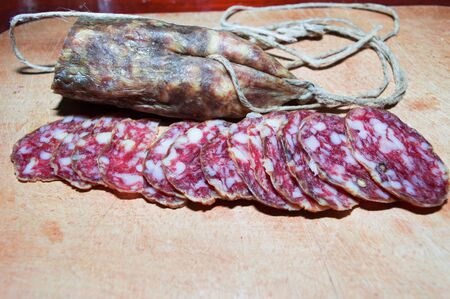 Closeup of dry sausage on a wooden tray