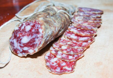 Dry salami on a wooden tray close up