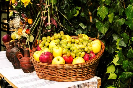 Autumn still life of fruit in a basket and a jug of wine