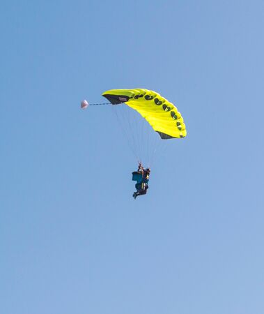 Yellow parachute against the blue sky with a skydiver