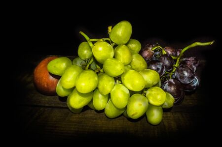 Grapes and apple on a wooden table 写真素材