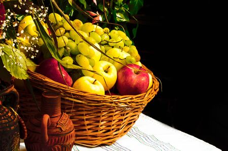 Wicker basket with fruits on a table on a dark background