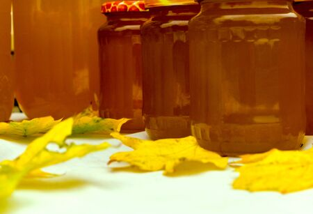 Honey in jars on a table with autumn foliage Stock fotó