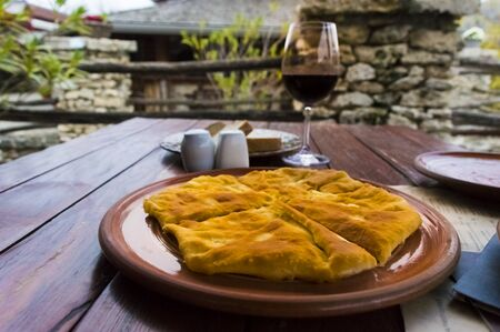 Glass of wine and hot placinta on a wooden table