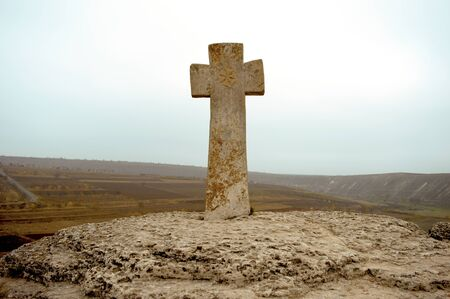 Stone cross on a cliff on a cloudy day near the monastery Imagens